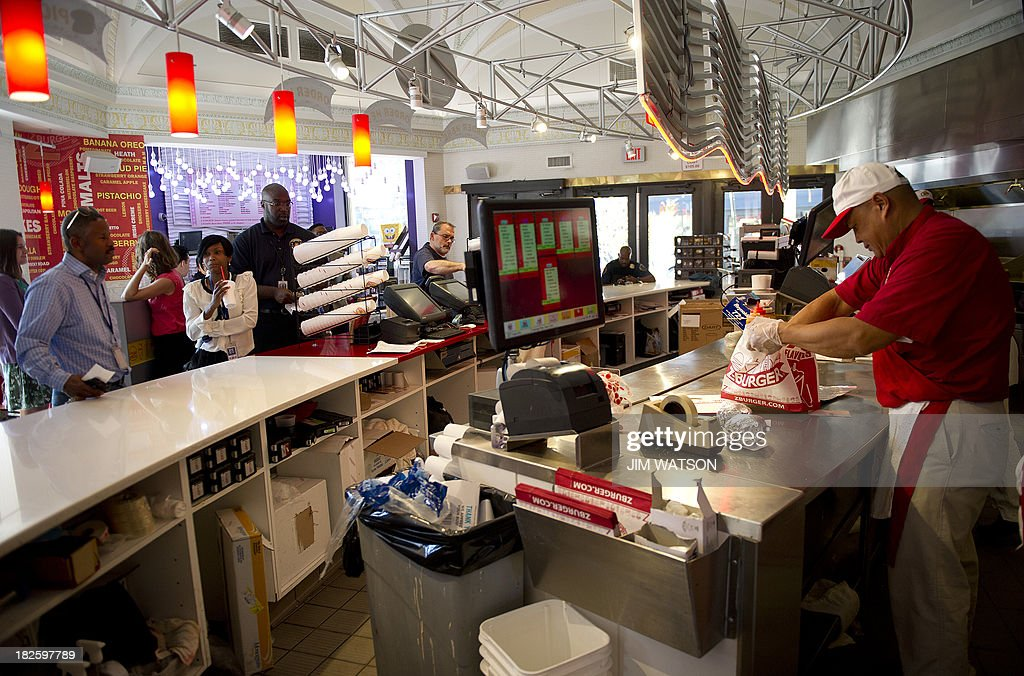 An employee at Z-Burger in Washington, DC, prepares food during the lunch hour rush October 1, 2013. The fast-food chain is promising free hamburgers to federal workers who find themselves furloughed after the US government shutsdown Tuesday, its founder and proprietor Peter Tabibian said. AFP PHOTO/Jim WATSON
