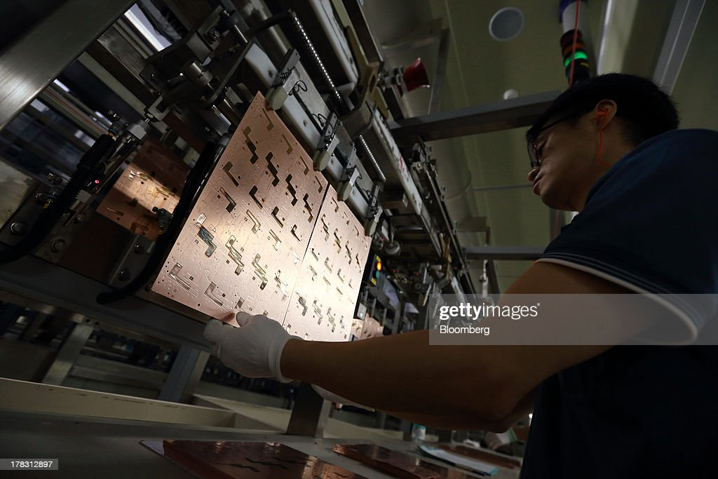 An employee attaches a Flexible Printed Circuit Board (F-PCB) panel onto a conveyor on the production line at the Seil Electronics Co. factory in Incheon, South Korea, on Wednesday, Aug. 28, 2013. South Korea has surpassed Brazil, Russia and India to become the second-biggest emerging stock market for the first time since 2006, as a stable won and record current-account surplus lure investors. Photographer: SeongJoon Cho/Bloomberg via Getty Images