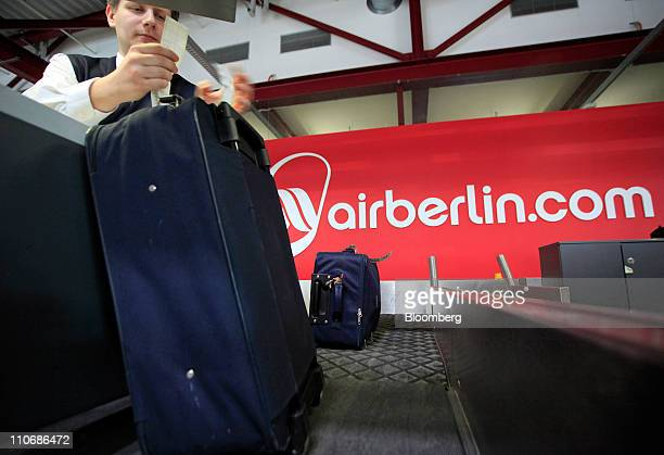 An employee attaches a label to luggage at the checkin counter of Air Berlin at Tegel airport in Berlin Germany on Wednesday March 23 2011 Air Berlin...