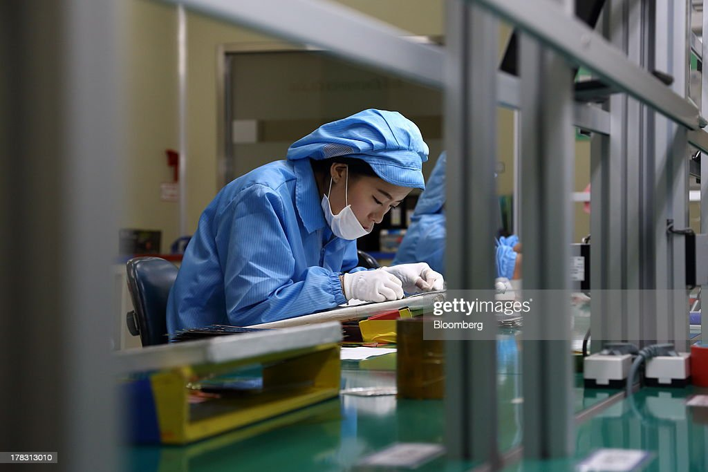 An employee attaches protective film to a Flexible Printed Circuit Board (F-PCB) panel on the production line at the Seil Electronics Co. factory in Incheon, South Korea, on Wednesday, Aug. 28, 2013. South Korea has surpassed Brazil, Russia and India to become the second-biggest emerging stock market for the first time since 2006, as a stable won and record current-account surplus lure investors. Photographer: SeongJoon Cho/Bloomberg via Getty Images
