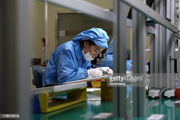 An employee attaches protective film to a Flexible Printed Circuit Board panel on the production line at the Seil Electronics Co factory in Incheon...