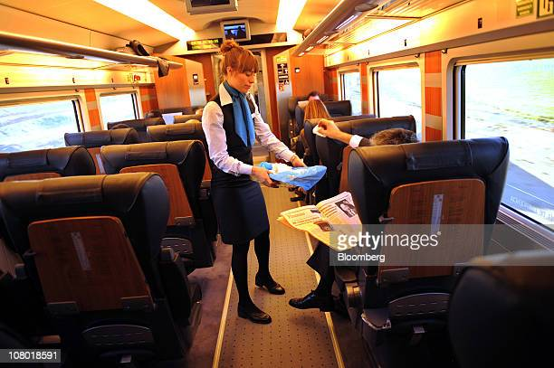 An employee attends a business class passenger travelling on board an Alta Velocidad Espanola highspeed on the Madrid to Valencia rail link in Spain...