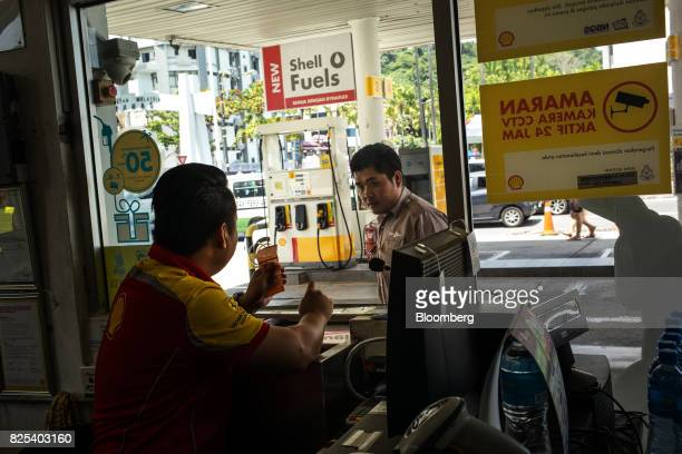 An employee attends to a customer at a Royal Dutch Shell Plc gas station in Kota Kinabalu in Sabah Malaysia on Sunday July 30 2017 Sabah and...