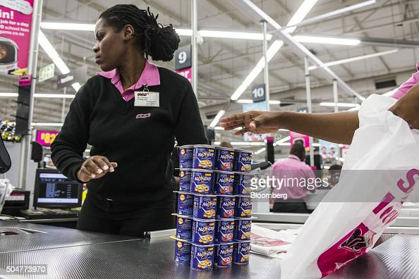 An employee bags cartons of Danone SA NutriDay products at the check out counter of a Game supermarket operated by Massmart Holdings Ltd at the...