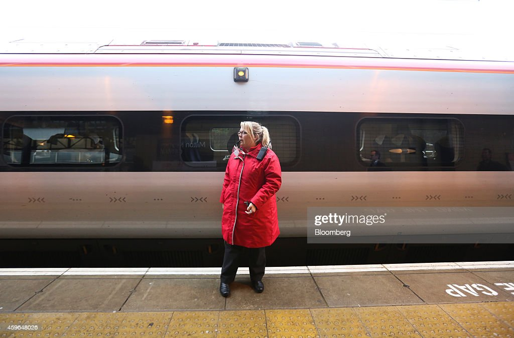 An employee blows a whistle as a West Coast train, operated by Virgin Trains, prepares to depart from a platform at Milton Keynes railway station in Milton Keynes, U.K., on Thursday, Nov. 27, 2014. Virgin Trains and partner Stagecoach Group Plc were chosen to run the London-Edinburgh rail route, fending off rival bids from FirstGroup Plc and Eurostar International Ltd. and delivering a boost for Richard Branson a month after the fatal crash involving his space venture. Photographer: Chris Ratcliffe/Bloomberg via Getty Images