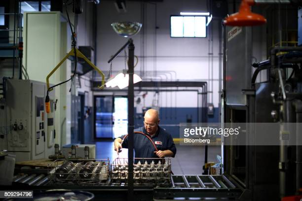 An employee blows gears while passing from one machine to the next at the SEWEurodrive Inc production facility in Lyman South Carolina US on Friday...