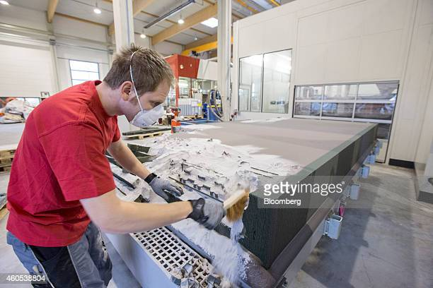 An employee brushes a 3D printing sand mold from a water jacket core automotive part during manufacture at the Voxeljet AG 3D printing plant in...