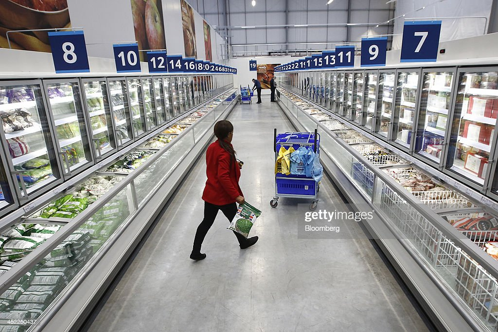 An employee carries a bag of frozen peas as she collects customer orders at a Tesco Plc on-line distribution center, in Erith, U.K., on Wednesday, Nov. 27, 2013. Tesco Plc, the U.K.'s largest retailer, will sell land near some of its Polish hypermarkets to attract additional services around those stores. Photographer: Simon Dawson/Bloomberg via Getty Images