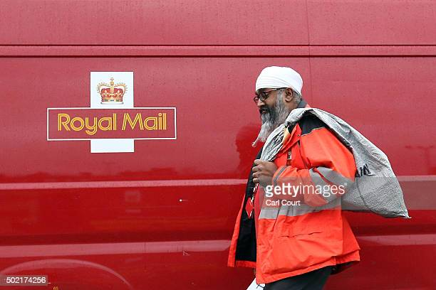 An employee carries a bag of mail alongside a a van at Royal Mail's Mount Pleasant Mail Centre on December 21 2015 in London England This week is...
