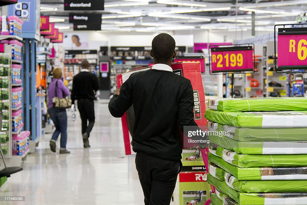 An employee carries a box containing a Weber barbecue inside a Game supermarket, part of Massmart Holdings Ltd., in the Fourways district of Johannesburg, South Africa, on Thursday, Aug. 22, 2013. Massmart Holdings Ltd., the South African food and goods wholesaler owned by Wal-Mart Stores Inc., said revenue growth continued to slow in August after a downturn in consumer spending hurt first-half earnings. Photographer: Nadine Hutton/Bloomberg via Getty Images