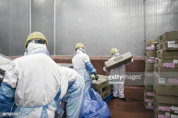 An employee carries a box containing imported Smithfield Foods Inc pork bellies which will be processed into bacon at the WH Group Ltd facility in...