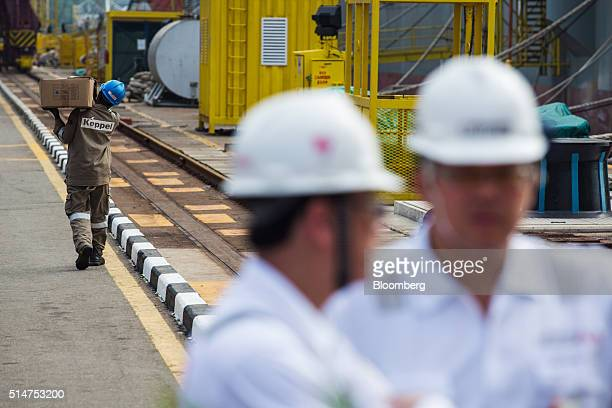 An employee carries a box near the Floatel Triumph a semisubmersible accommodation rig operated by Floatel International Ltd and developed by Keppel...