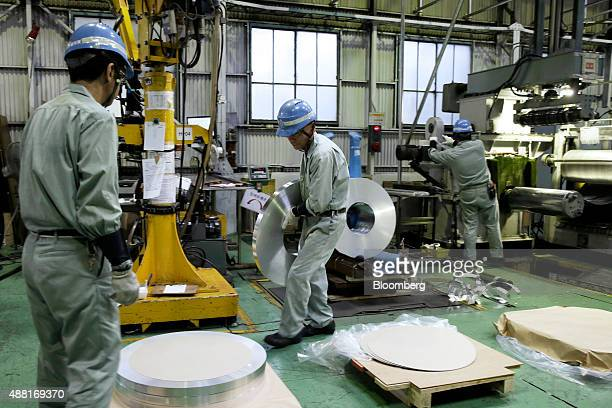 An employee carries a coil of aluminum strip to be packaged at the Tokiwa Koutai Co processing plant in Tokyo Japan on Friday Aug 7 2015 Prime...