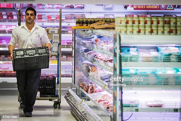 An employee carries a crate inside a Coles supermarket operated by Wesfarmers Ltd in Sydney Australia on Tuesday Feb 18 2014 Wesfarmers Australia's...