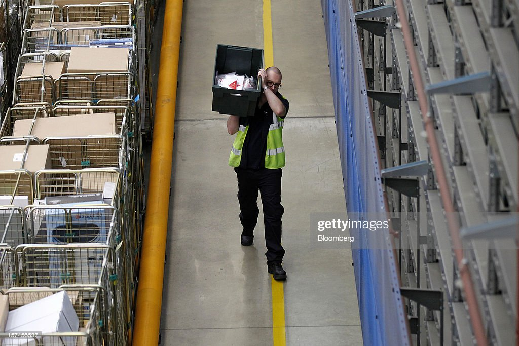 An employee carries a crate of goods inside John Lewis Plc's semi-automated distribution centre in Milton Keynes, U.K., on Monday, Dec. 3, 2012. An index of U.K. retail sales rose to a five-month high in November, according to a monthly report from the Confederation of British Industry. Photographer: Simon Dawson/Bloomberg via Getty Images