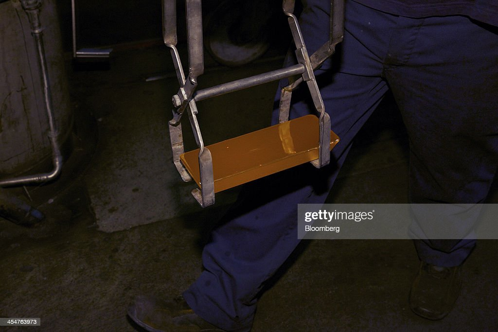 An employee carries a freshly cast 400 ounce gold bar to a water cooling bay during the semiautomated gold bar manufacturing process at a precious...