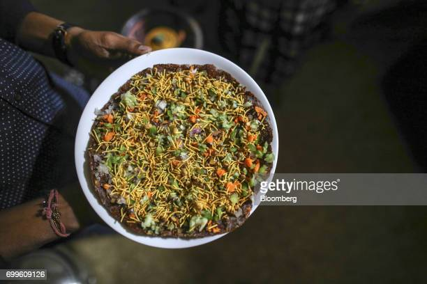 An employee carries a khakra a thin pancake made from millet at the Vaathsalya Millet Cafe in Bengaluru India on Saturday June 10 2017 Millets were a...
