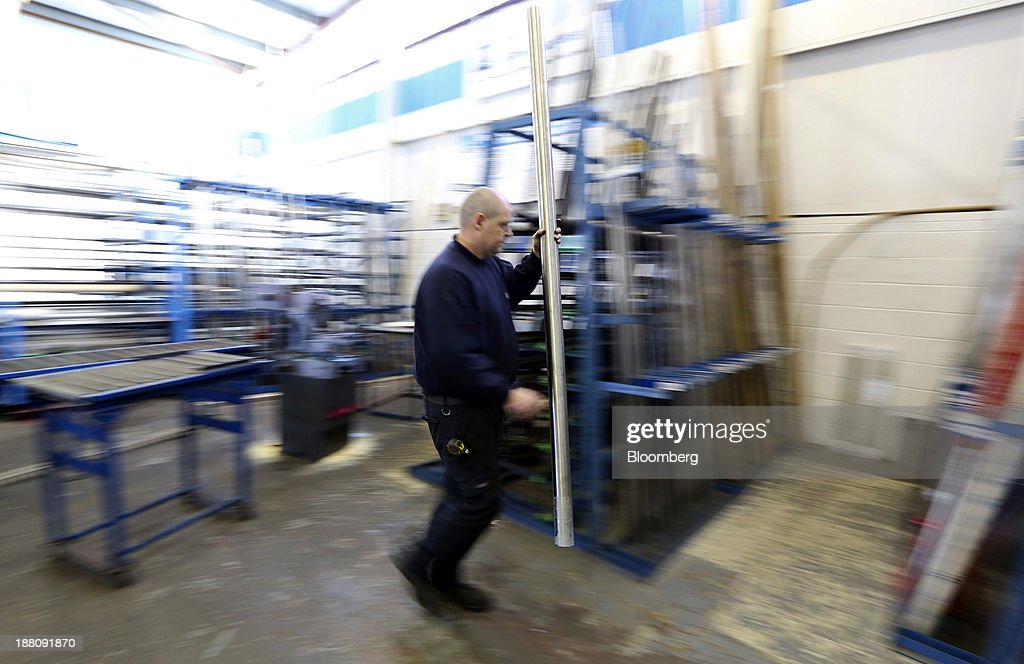 An employee carries a length of metal through the warehouse at Metal Supermarkets in Southampton, U.K., on Friday, Nov. 15, 2013. The Bank of England sees gross domestic product rising 0.9 percent this quarter before easing in the early part of 2014, according to its new projections. Photographer: Chris Ratcliffe/Bloomberg via Getty Images
