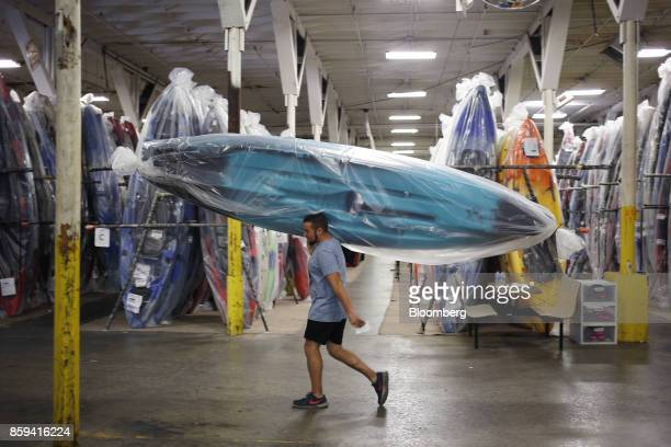 An employee carries a newly manufactured plastic kayak towards the loading dock at the Jackson Kayak Inc factory in Sparta Tennessee US on Wednesday...