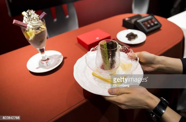An employee carries a plate of frozen KitKat dessert next to a glass of parfait during a media preview of the KitKat Chocolatory Ginza store operated...