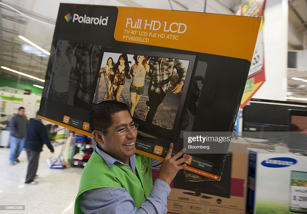 An employee carries a Polaroid Corp. 40 inch LCD television to a cash register inside Wal-Mart de Mexico SAB de CV's Bodega Aurrera store in Mexico City, Mexico on Saturday, Nov. 17, 2012. El Buen Fin, Mexico's equivalent of Black Friday, when the year's biggest discounts are offered by participating stores, is held on the third weekend of November and will run through Nov. 19. Photographer: Susana Gonzalez/Bloomberg via Getty Images
