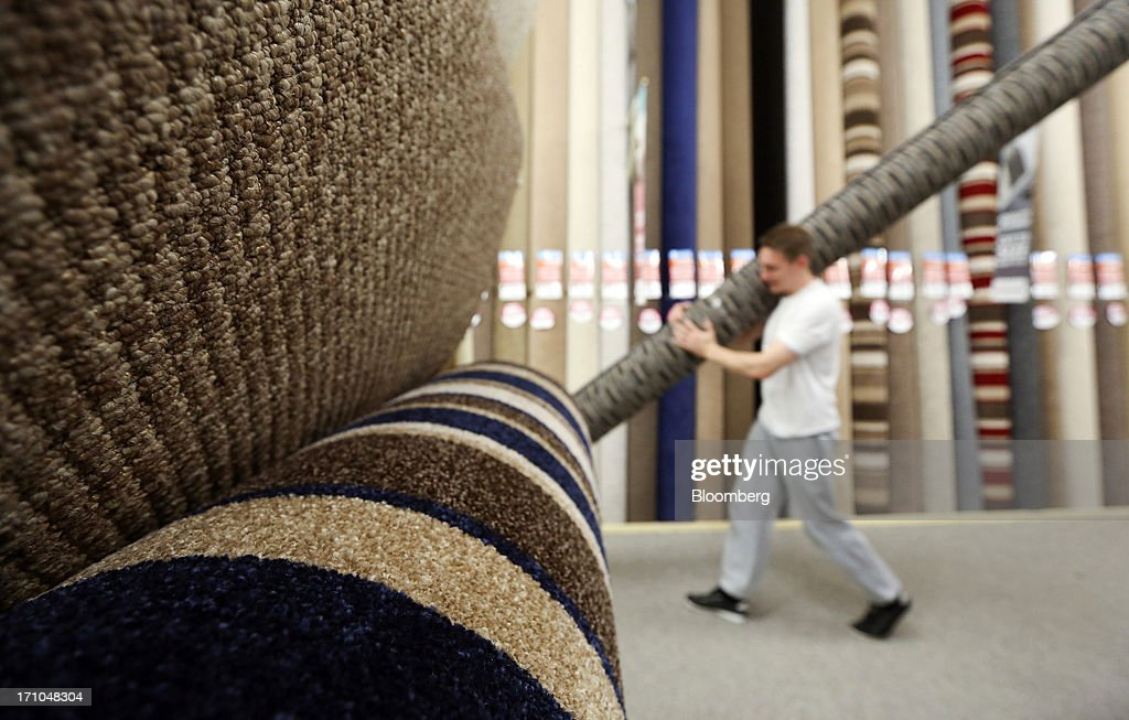 An employee carries a roll of carpet past a display of pre-cut carpet rolls inside a Carpetright Plc store in Basildon, U.K., on Friday, June 21, 2013. U.K. retail sales rose more than economists forecast in May as consumers spent more online and food sales increased at their fastest pace for more than two years. Photographer: Chris Ratcliffe/Bloomberg via Getty Images