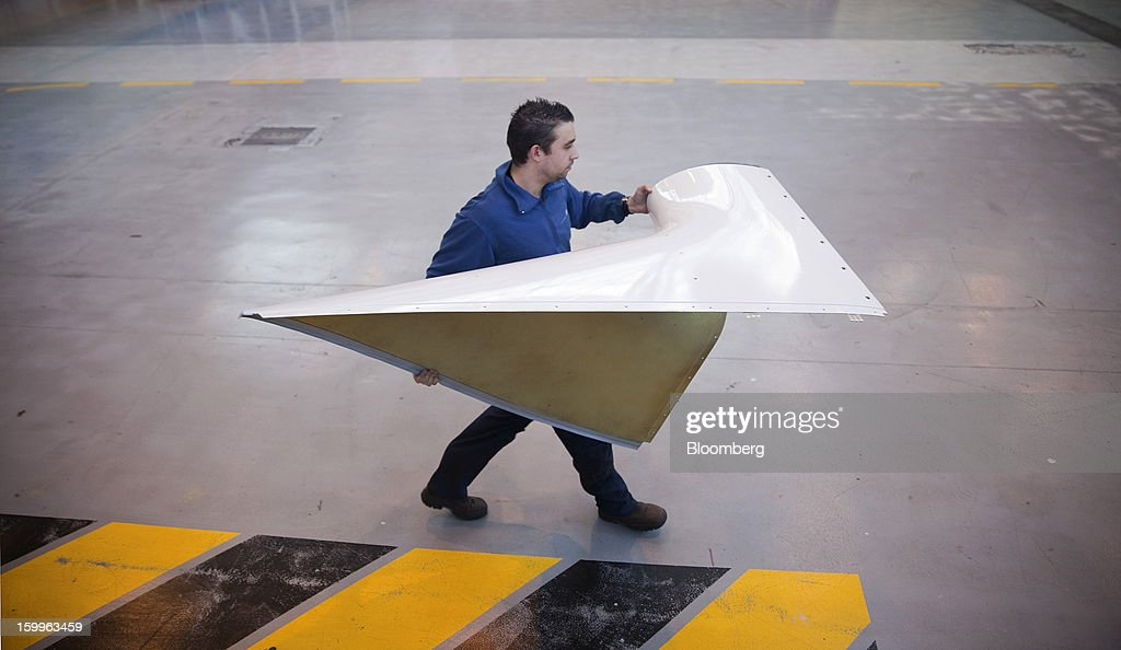 An employee carries a section of fuselage during the construction of an ATR-72 turboprop aircraft, manufactured by Avions de Transport Regional (ATR), at the company's production facility in Colomiers, France, on Wednesday, Jan. 23, 2013. ATR, the world's largest maker of turbo-propeller airliners, reported record profit for 2012, even as it fell short of its shipment target amid production delays. Photographer: Balint Porneczi/Bloomberg via Getty Images