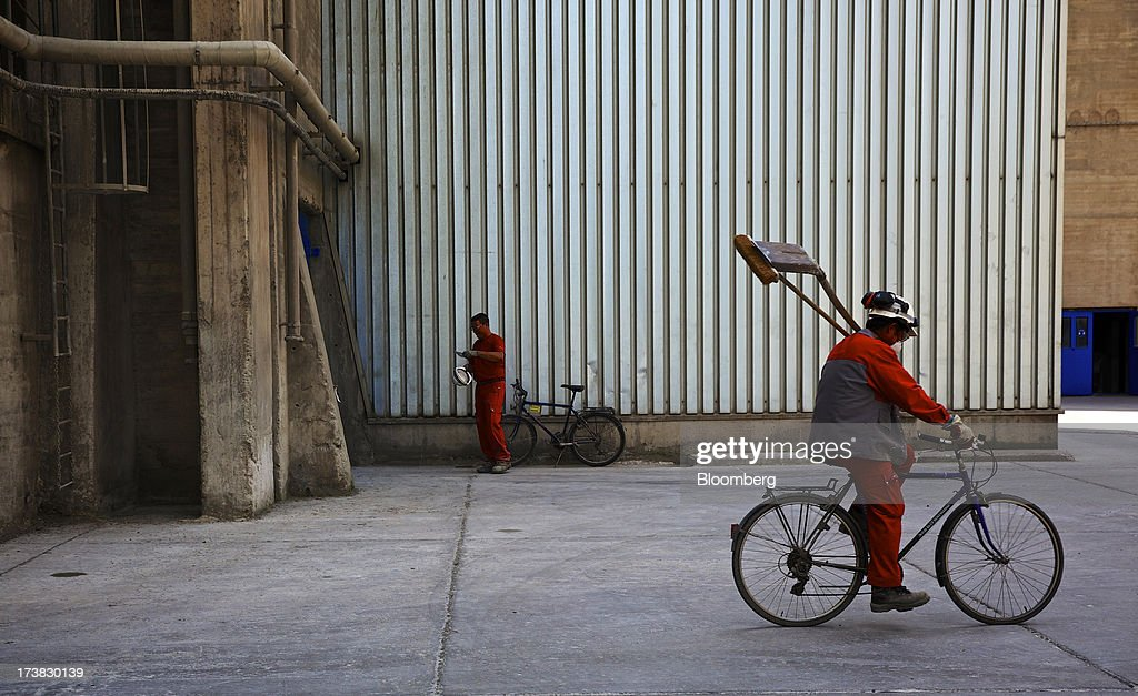 An employee carries a shovel and a brush as he cycles across the yard at Holcim Ltd.'s cement plant in Untervaz, Switzerland, on Wednesday, July, 17, 2013. Holcim Chief Executive Officer Bernard Fontana has cut costs and expanded in emerging regions such as Latin America and Indonesia to counter a construction slump in Europe, caused by the region's economic crisis. Photographer: Gianluca Colla/Bloomberg via Getty Images