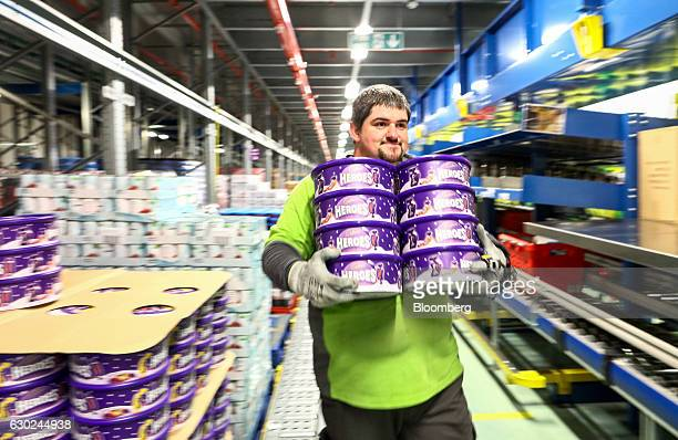 An employee carries a stack of heroes chocolates manufactured by Cadbury Ltd as he picks an order at the Ocado Group Plc distribution centre in...