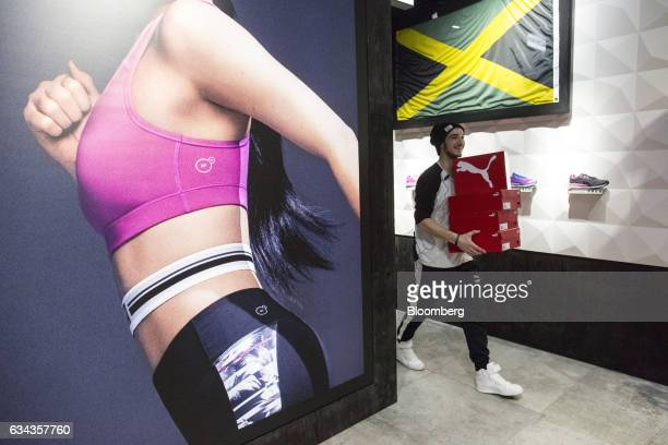 An employee carries a stack of shoeboxes inside the Puma SE concept store at the sportswear company's headquarters in Herzogenaurach Germany on...