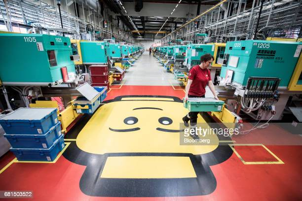 An employee carries a storage box of Lego toy bricks from the moulding machines on the production line at the Lego A/S plant in Nyiregyhaza Hungary...