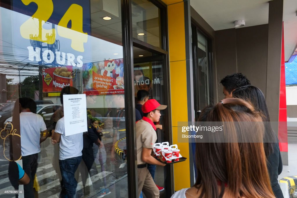 An employee carries a tray of drinks as customers wait to enter a Jollibee Foods Corp. restaurant in Quezon City, Metro Manila, the Philippines, on Monday, July 28, 2014. Jollibee, which outsells McDonald's Corp. in the Philippines, plans to double earnings in five years as it accelerates its expansion in China and seeks an acquisition in the U.S. Photographer: Veejay Villafranca/Bloomberg via Getty Images