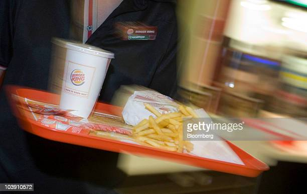 An employee carries a whopper meal through a Burger King restaurant in Basildon UK on Wednesday Sept 8 2010 Burger King Holdings Inc agreed to be...