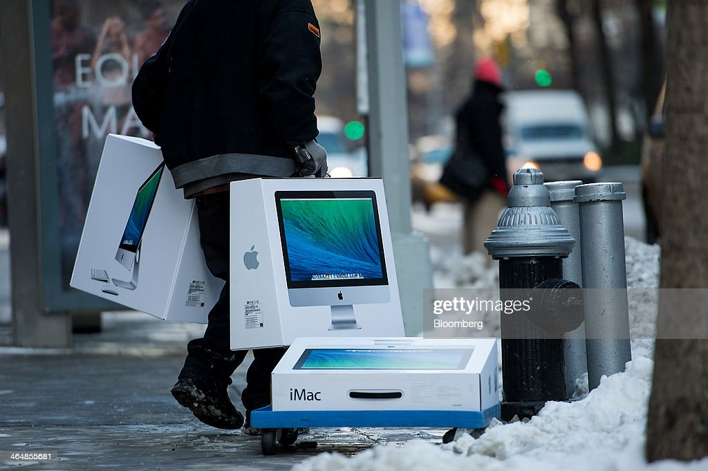 An employee carries Apple Inc. iMac computers outside s store in New York, U.S., on Thursday, Jan. 23, 2014. Billionaire investor Carl Icahn said he increased his stake in Apple Inc. by another $500 million, bringing his total holdings in the iPhone maker to about $3.6 billion as he reiterated calls for a bigger stock buyback. Photographer: Ron Antonelli/Bloomberg via Getty Images