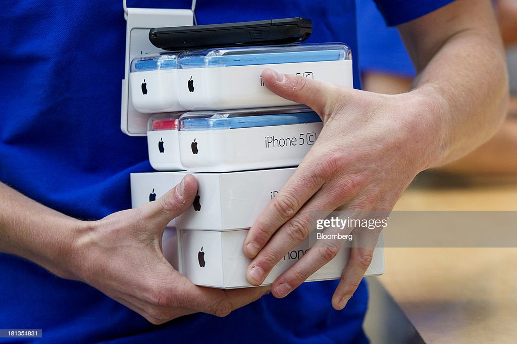 An employee carries Apple Inc. iPhone 5c and 5s devices during the launch at the company's new store in Palo Alto, California, U.S., on Friday, Sept. 20, 2013. Apple Inc. attracted long lines of shoppers at its retail stores today for the global debut of its latest iPhones, in the company's biggest move this year to stoke new growth. Photographer: David Paul Morris/Bloomberg via Getty Images
