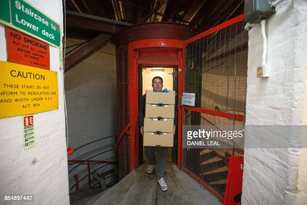 An employee carries boxes of microgreen salad from the elevator at the urban farm project 'Growing Underground' in Clapham south London on September...