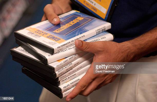 An employee carries game cartridges and DVD movies at a Blockbuster Video store November 19 2002 in the Little Havana section of Miami Florida...