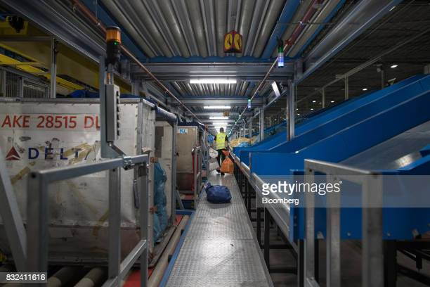 An employee carries mail sacks down a walkway at the KLM Cargo center operated by Air FranceKLM Group at Schiphol airport in Amsterdam Netherlands on...