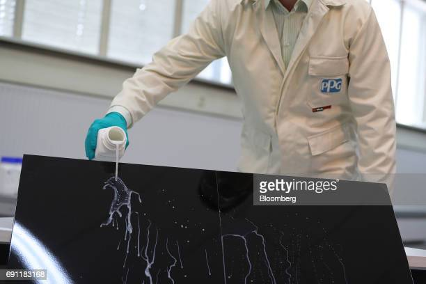 An employee carries out a PPG clearcoat coating liquid demonstration inside PPG Industries Inc's automotive coating's technical center in Ingersheim...