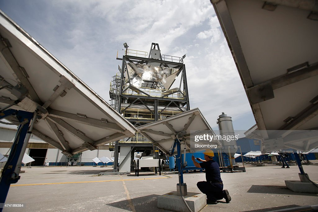 An employee carries out maintenance work on a heliostat panel as a solar generation unit stands beyond at a Solar Thermoelectric Magaldi (STEM) pilot plant, operated by Magaldi Group, in Buccino, Italy, on Monday, May 18, 2015. The project captures the energy of the sun which is transferred via the generation unit to heat retaining silica sand, producing steam that powers a turbine and is suitable for use in systems operating over a large temperature range. Photographer: Alessia Pierdomenico/Bloomberg via Getty Images