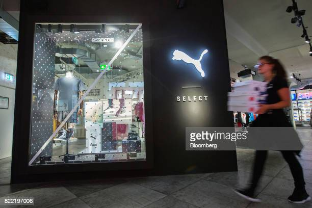An employee carries shoe boxes inside a Puma SE sportswear clothing store in Berlin Germany on Tuesday July 25 2017 Puma increased its fullyear...