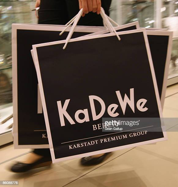 An employee carries shopping bags in this photo illustration at the KaDeWe luxury department store on April 21 2009 in Berlin Germany German retail...