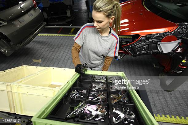 An employee carries the badges of a Peugeot 2008 SUVs at the PSA Peugeot Citroen assembly plant on March 14 2014 in Mulhouse France Chinese automaker...