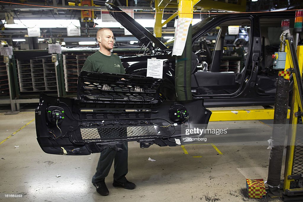 An employee carries the front grill of a Land Rover Freelander 2 SUV automobile, produced by Jaguar Land Rover Plc, a unit of Tata Motors Ltd., as it travels along the production line at the company's assembly plant in Halewood, U.K., on Wednesday, Feb. 13, 2013. Carmakers from Ford Motor Co. to Audi AG and Jaguar Land Rover Plc are using record amounts of aluminium to replace heavier steel, providing relief to producers of the metal confronting excess supplies and depressed prices. Photographer: Simon Dawson/Bloomberg via Getty Images