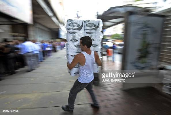 An employee carries toilet paper as we walks towards a pharmacy in Caracas on October 22 2015 The Venezuelan government limited the gain in business...