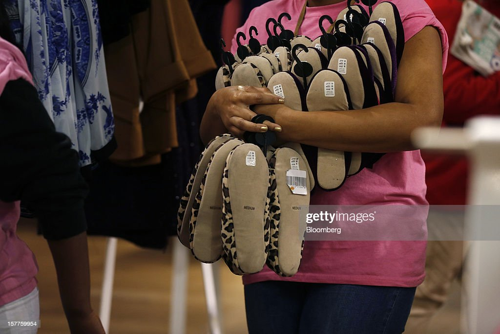 An employee carries women's slippers to re-stock a display inside a Topshop store, owned by Arcadia Group Ltd., on Oxford Street in London, U.K., on Thursday, Dec. 6, 2012. Philip Green, the billionaire owner of the Arcadia fashion business, sold a 25 percent stake in the Topshop and Topman retail chains to Leonard Green & Partners LP, the co-owner of the J Crew fashion brand, in a deal valuing the businesses at 2 billion pounds ($3.2 billion). Photographer: Simon Dawson/Bloomberg via Getty Images