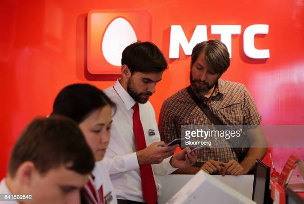 An employee center assists a customer at a service desk inside a Mobile TeleSystems PJSC mobile communications store in Moscow Russia on Friday Sept...