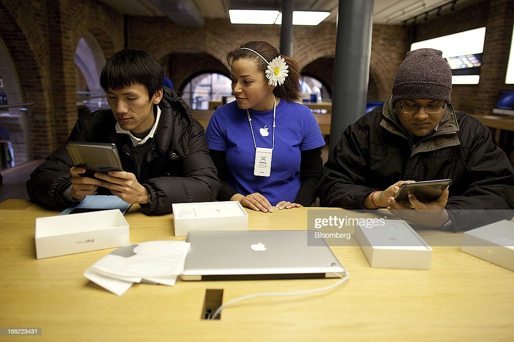 An employee, center, assists customers inspecting new Apple Inc. iPad minis at the company's Covent Garden store in London, U.K., on Friday, Nov. 2, 2012. Apple Inc.'s iPad mini tablet goes on sale in the U.K. today. Photographer: Simon Dawson/Bloomberg via Getty Images