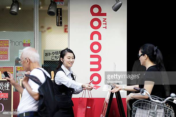 An employee center hands out free promotional pocket tissues to passing pedestrians outside an NTT Docomo Inc store in Tokyo Japan on Monday Sept 14...