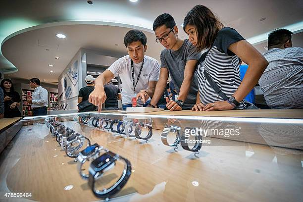 An employee center left assists customers looking at Apple Inc Apple Watch smartwatches on display at an Epicentre Holdings Ltd store in the Ion...